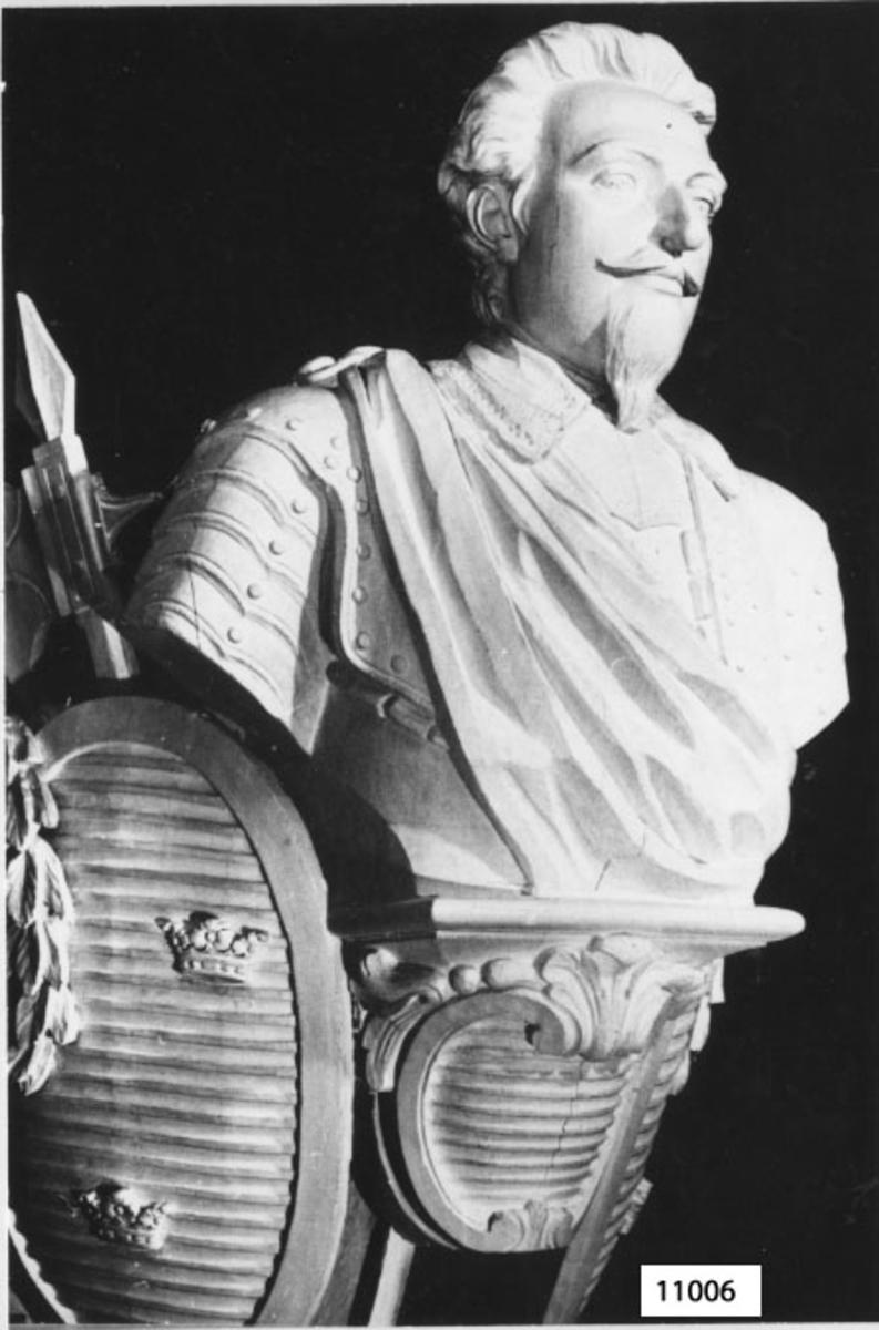 Galjonsbild tillhörande linjeskeppet Gustaf den Store. Byst av mansperson (Gustaf II Adolf) med mustasch och pipskägg samt bakåtkammat hår, iförd rustning, draperad över högra axeln. I halsen spetskrage. Bysten är på varje sida garnerad med oval 3-kronors sköld med överhängande lagerkrans. Bakom skölden döljs stridsyxa, svärd och fana.