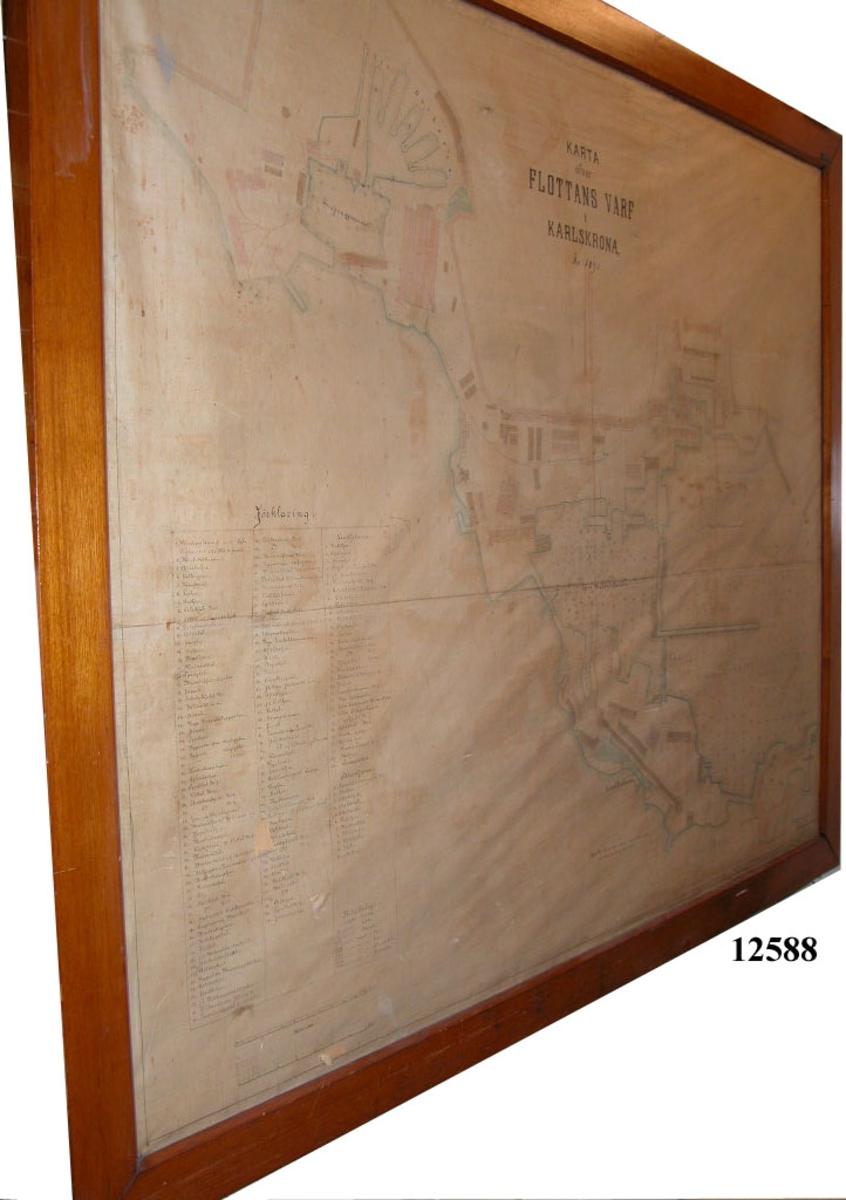 Karta ritad på väv och färglagd. Text: Karta över Flottans Varf i Karlskrona 1895. Inom glas och ram.