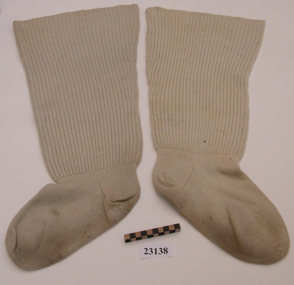 Ett par strumpor, lårhöga, av medeltunnt benvitt yllegarn. Foten slätstickad, skaften ribbstickade, ingen resår.