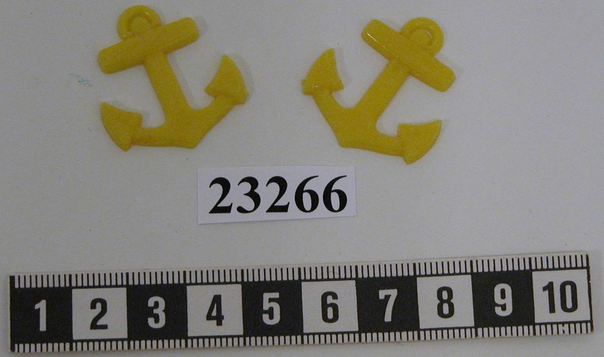 Yrkestecken för manskap vid däcksavdelningen (ett par) i form av gula stockankare i plast utan tross. Ankaret är 39 mm högt , 31 mm brett och 2 mm tjockt.
