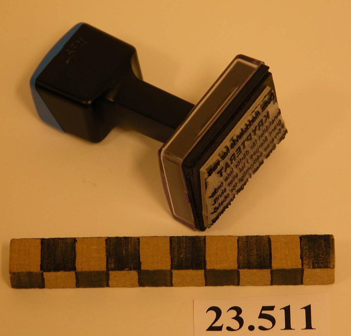 Stämpel bestående av svart och blått plasthandtag, rektangulär form. Stämpelfot rektangulär form av transparant plast med gummidyna. På stämpelfotens ovansida vitt papper med svart text som återfinns på stämpeldynan: Detta meddelande har varit KRYPTERAT innehållet får därför inte ordagrant återges i tal eller skrift. Förvaras oåtkomligt för obehöriga. Svar skall i regel krypteras. Rund svart etikett på handtaget anger tillverkare: HAMMARGRENS STÄMPLAR *040-103880* BOX 6066 20011 MALÖMÖ.