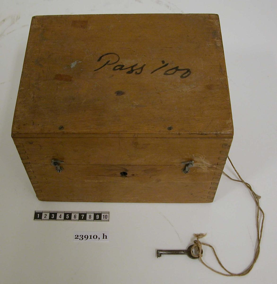 """Låda av trä med lås och tillhörande nyckel. På högra kortsidan sitter ett handtag av metall. På framsidan sitter två haspar. I lådan sitter filtklädda delar till prövningsinstrumentet samt för reservlinser i locket. På lockets insida sitter en handskriven papperslapp försedd med texten """"Prövningsinstrument för stereoskopiskt seende"""", """"Nr. 8079"""" samt """"Kungl. Marinförvaltningen"""". På lockets ovansidan finns texten """"Pass 100"""", skrivet med svart tusch."""