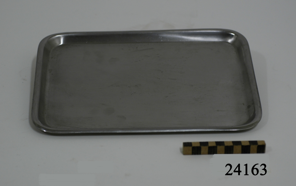 """Rektangulär bricka av rostfritt stål med 2 cm breda, något uppböjda kanter. På baksidan graverat i godset: """"KIFA SWEDEN ROSTFRITT STÅL S.S.""""."""
