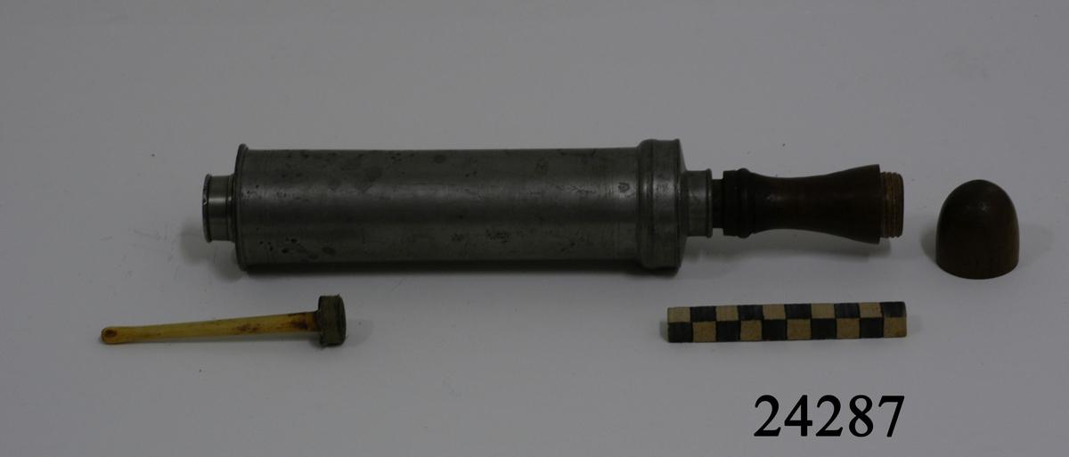 Cylinderformad lavemangsspruta, kronstämplad, av tenn med pump och svarvat handtag av trä. Handtaget delbart, fungerar som behållare till 10 cm lång pip av ben med rundad topp. I sprutans främre del en rund, kort tapp med hål. I den bakre delen ett gängat lock med hål för pumpen. På locket fem stycken otydliga stämplar.