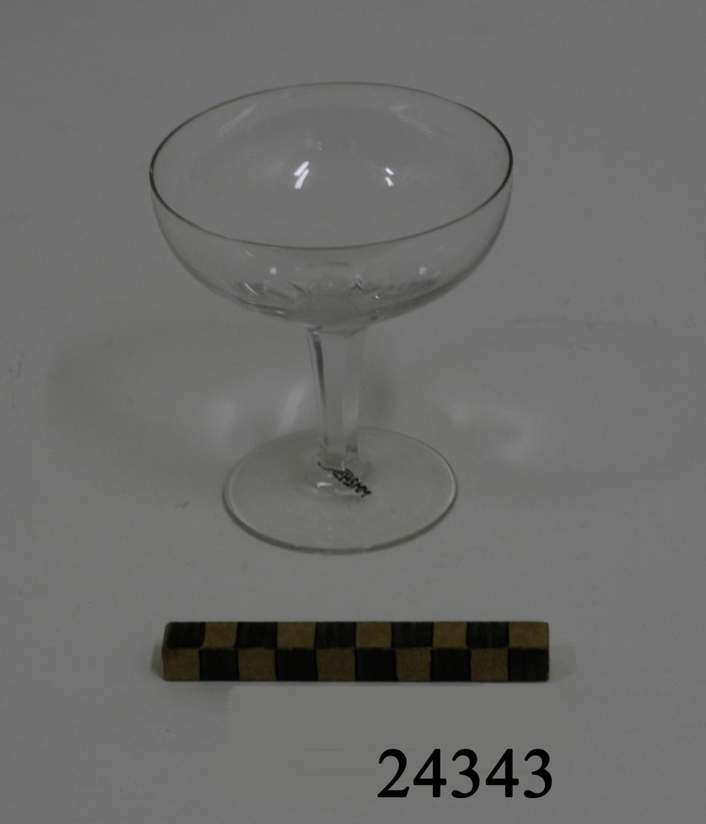 Champagneglas med välvd låg kupa. Smalt, fasettslipat ben. Rund, plan fot. På kupan, inetsat, lilla riksvapnet.
