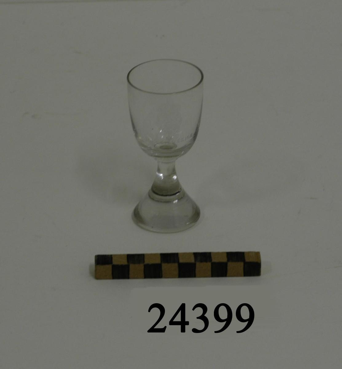"""Sherryglas bestående av smal cylindrisk kupa och konformad massiv fot. Mitt på kupan graverad dekor: lilla riksvapnet omgivet av koldinerorden. Därunder text: """" H.M.S. SVERIGE """" Diameter: 45 mm, glaset  D = 42 mm, fot"""