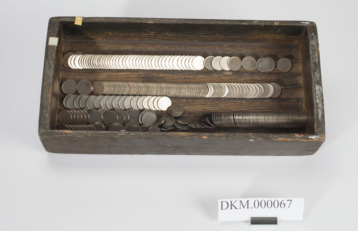 Rektangulær, åpen kasse med langsgående riller til plassering av mynt i bunnen.
