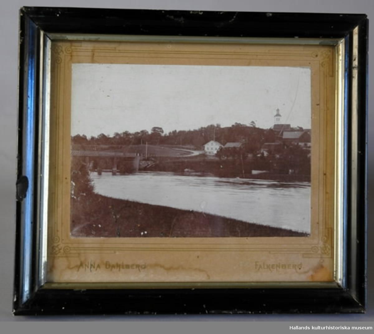 """Fotografi i ram. Motiv föreställande ån Ätran och Vessigebro gamla bro över ån. Några hus samt Vessige kyrka i bakgrunden. Ram av mörkt/svart trä. Passepartouten är märkt """"ANNA DAHLBERG, FALKENBERG"""". Ramens bredd 2 cm."""