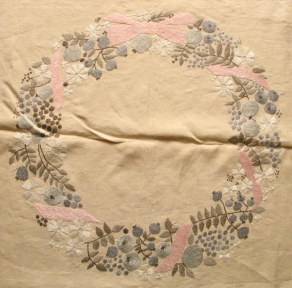 Broderad kvadratisk storduk. Sydd på beigefärgat Ölandsllinne med lingarn i grå, beige, rosa  och vita nyanser. Sydd efter påritat mönster. Krans med grå äpplen och vita blommor. Rosa band och rosett runt kransen.
