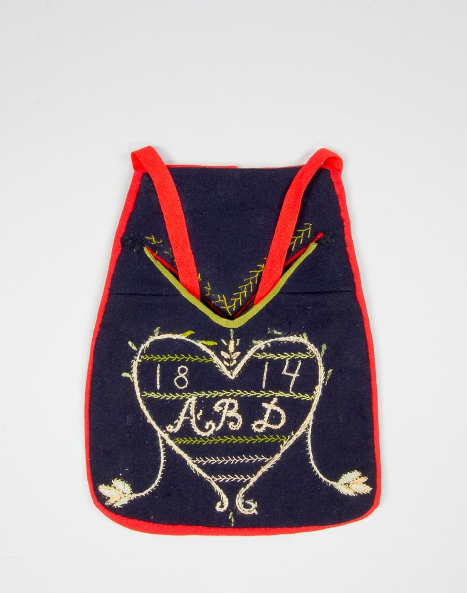 Kjolsäck till dräkt för kvinna från Unnaryds socken, Västbo härad, Småland. Modell med v-formad öppning, med passande lock. Tillverkad av mörkblått ylletyg, kläde. På framstycket broderi utfört med silkegarn i ljusa nyanser rosa, grönt och ljusblått: kedjesöm, langettsöm, plattsöm, kråkspark och  stjälksöm. Motiv: hjärta omgivet av bladornament, inuti fyllt med rader av av stygn, dessutom monogram: A B D, samt årtalet 1814, som kanske syftar på det årtal förlagan hade. Kantad runtom med en remsa rött kläde. Den v-formade öppningen är försedd med en remsa grönt diagonalvävt band av bomull längs nedre kanten. På ficklocket en remsa rött kläde längs kanten. Kråksparksbroderi längs kanten. Baksida av kypertvävt tyg, troligen handvävt, randigt i blått och beige på svart botten, brun varp. Midjeband fabriksvävt, av röd diagonalvävd ulll.