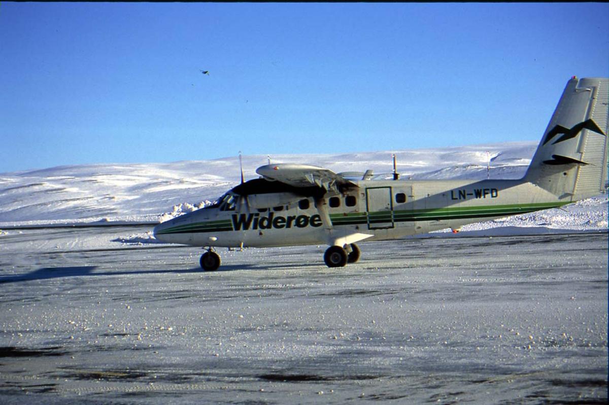 """Lufthavn. 1 fly på bakken. 1 DHC-6 Twin Otter LN-WFD """"Båtsfjord"""" fra Widerøe, sett fra siden. Fjell i bakgrunnen. Snø på bakken."""
