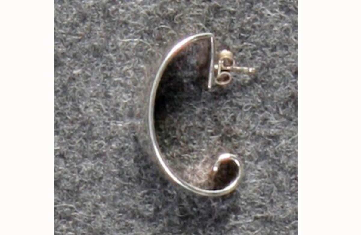 Består av to i bredden konvekse sølvbånd, lagt på hverandre med avstand mellom. Bånd er festet til hverandre og avtar mot hver ende. Stor åpning mellom de to endene. Ørefeste i den ene enden.