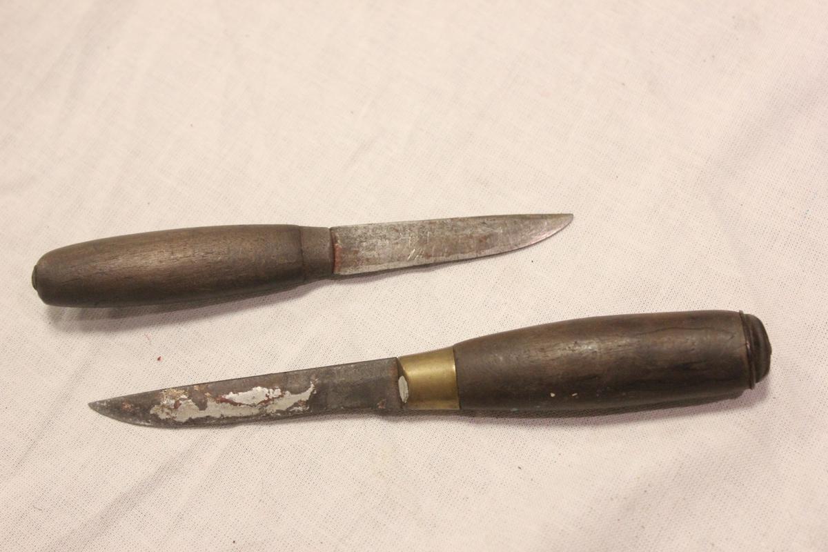 To små tollekniver laget av tre og jern. Ingen farge. A: Har smal, ikke så lang kniv. Den går helt gjennom skaftet og er festet bakerst i skaftet. Mellom kniv og skaft en liten ring. Vanlig treskaft. Merket på kniven: MOARA. B: Har smal litt lang og spiss kniv. Den går helt gjennom skaftet og er festet bakerst i skaftet. Mellom kniv og skaft en bred ring. Vanlig treskaft. A: Lengde kniv: 13,8 cm, skaft: 7,6 cm, blad: 6,2 cm. B: Lengde kniv: 16,7, skaft 8,9 cm, knivblad 7,8 cm.