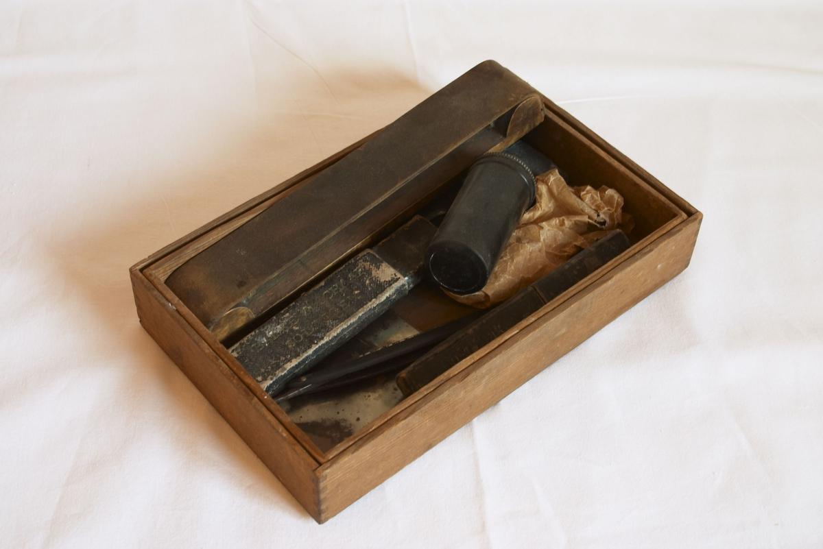 Et tre-skrin med bunn og lokk. I dette skrinet finnes forskjellig barberingsutstyr.