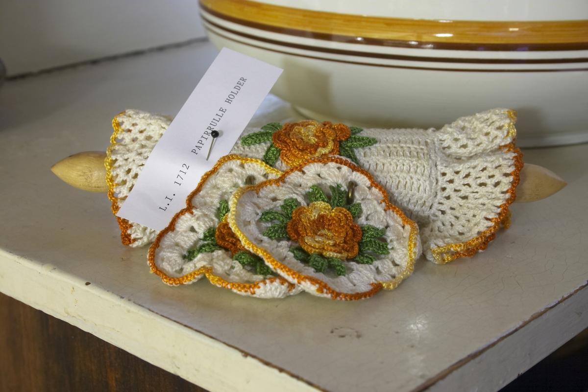 Til å sette på toalett-rullen. Papirrulleholder. Et lite kjevleformet trestykke som det er påsatt en helket duk med blonder i sidene og blomstermønster samt en hank til åhenge papirrulleholderen opp i. ellers er to heklede rosetter satt på to kroker som står i papirrulleholderen.
