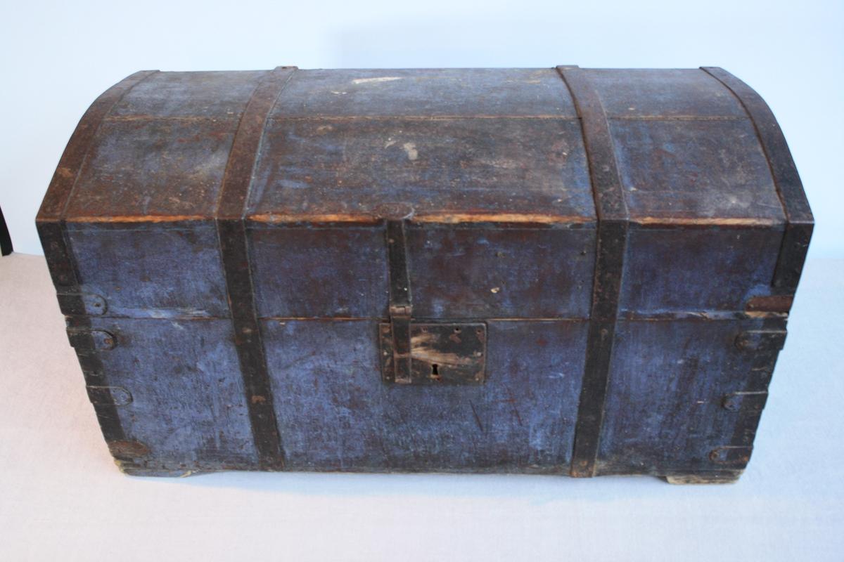 Gråblå kiste med bua lok og metallbeslag. Har ein leddik utan lok. Hengsla bunn av loket som gir eit oppbevaringsrom (målt oransje). Kjem frå rom 2 i Ausevika.