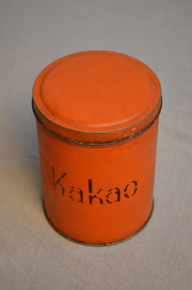 Rund boks for oppbevaring av matvarer. Oransje farge. Det står Kakao på boksen. Målinga er skrapt av enkelte plassar. I boksen låg det ein pakke med kakao. Den har fått reg.nr. KSF.011244. Har blitt lagt opp igjen i boksen.