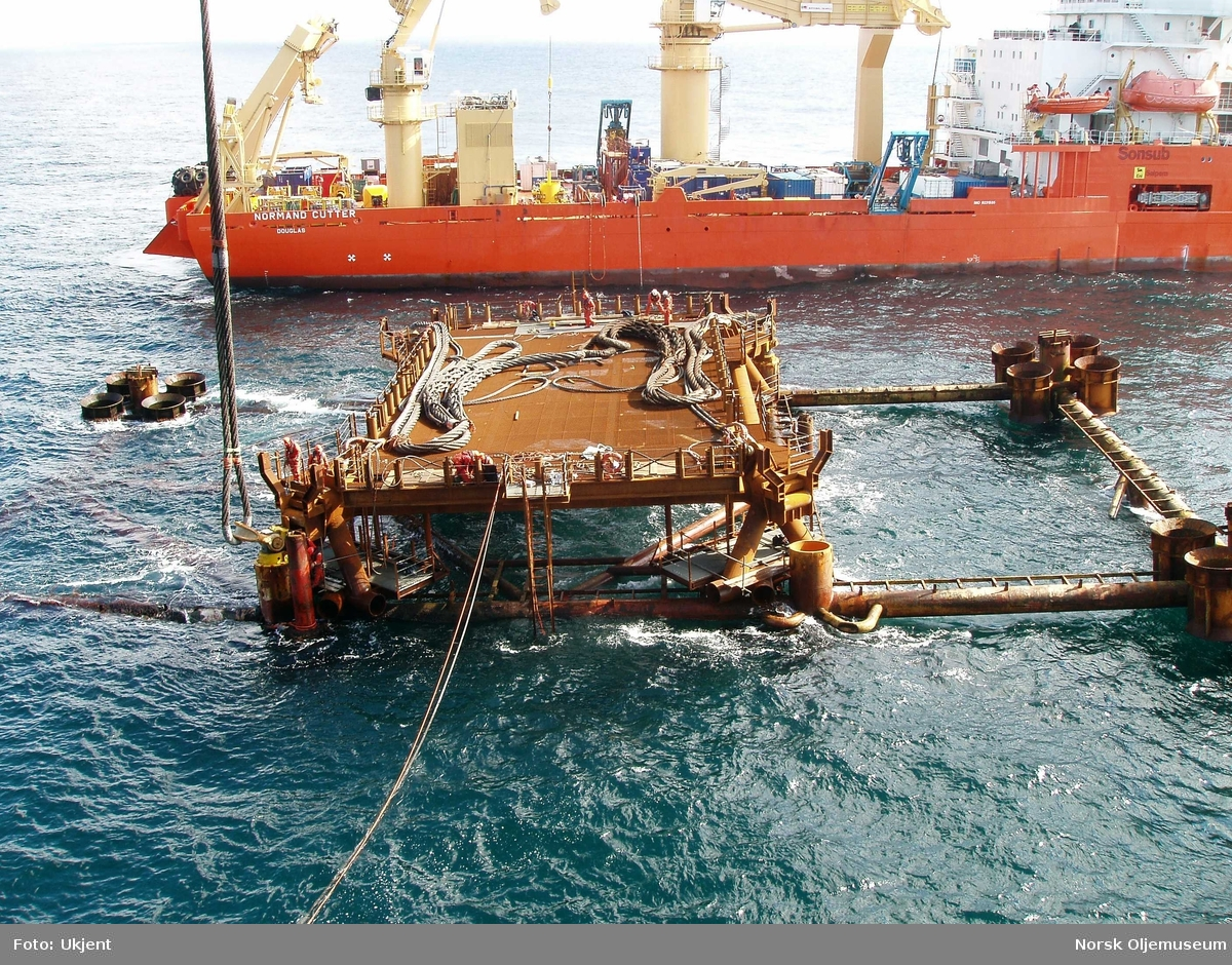Forberedelsene til fjerningen av stålunderstellet til DP1 - det såkalte vraket på Frigg-feltet er i gang.  Et arbeidsdekk er plassert på vraket, og fra dette kan det jobbes med å klargjøre fester for kranlekteren som senere skal løfte understellet opp fra havbunnen.