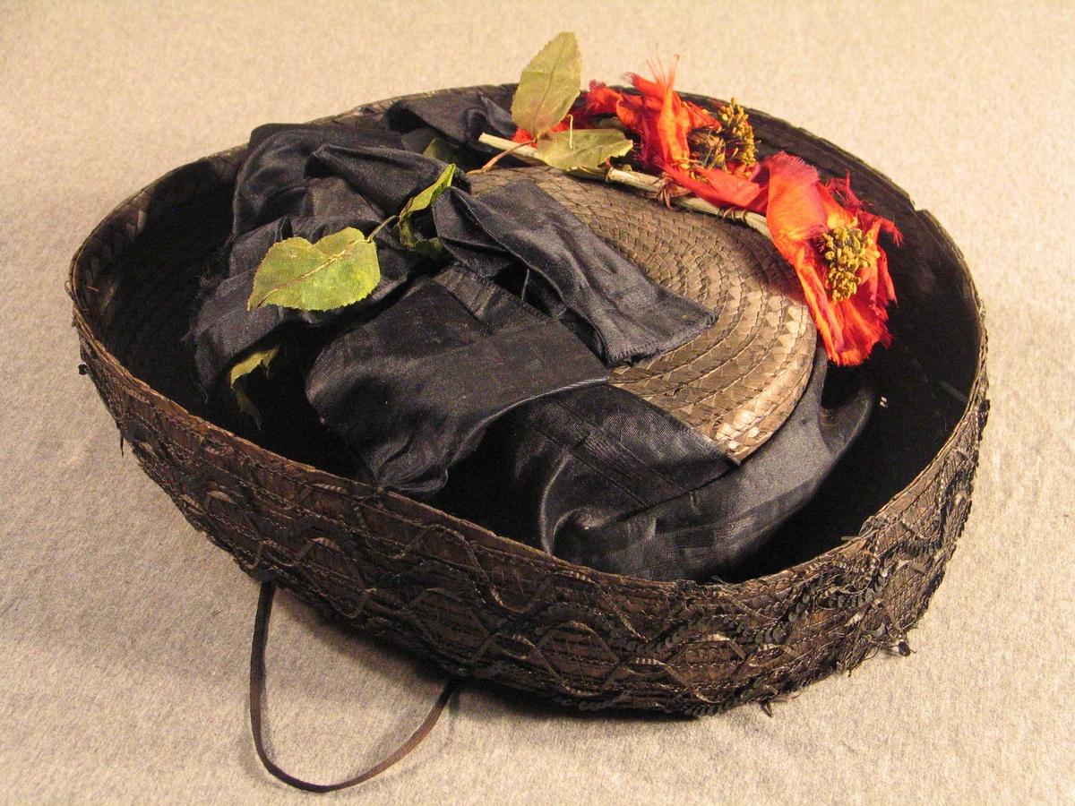 Stor svart silkesløyfe rundt pullen, raude silkeblomster, grøne blad av voksa papir. Bremmen er dekorert med svarte paljettar, stråband og netting.