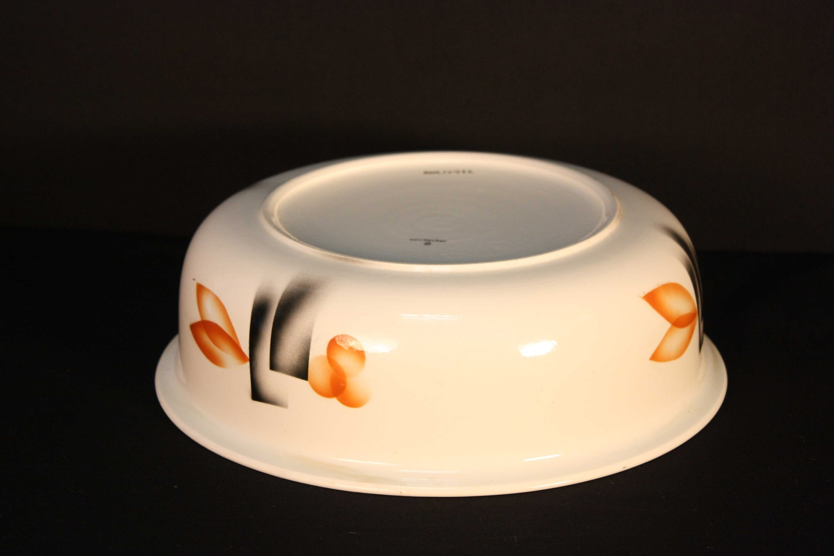 Vaskefat som høyrer til eit vaskestell av fat, mugge og såpekopp (SUM.10472-10474). Flat botn over ein låg stett, krumma korpus med utovervend munning. Jugendinspirert dekor.