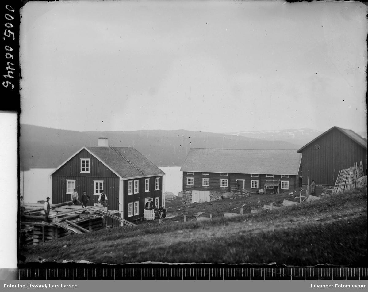 Oversiktsbilde av et gårdstun og lafting av ny bygning.