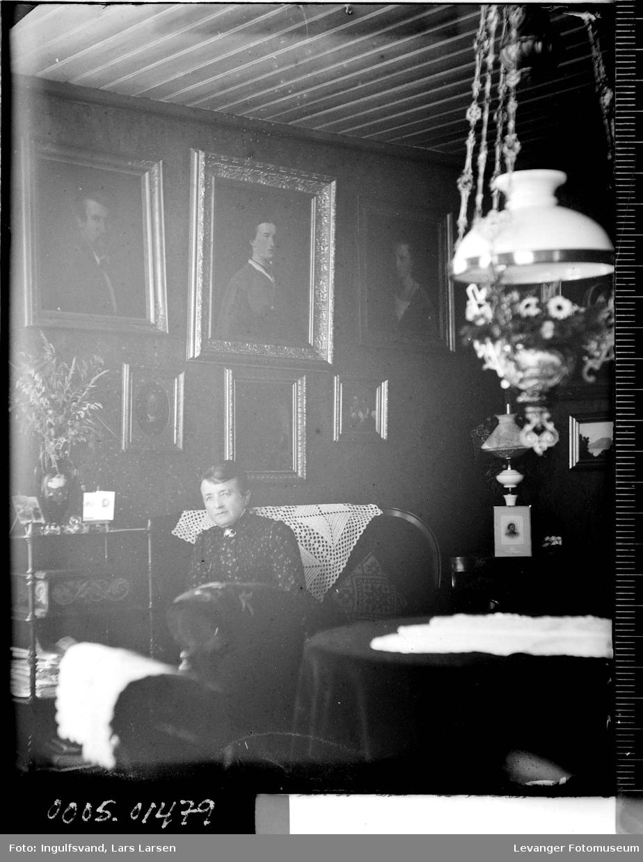 Portrett av en kvinne som sitter i en stue.