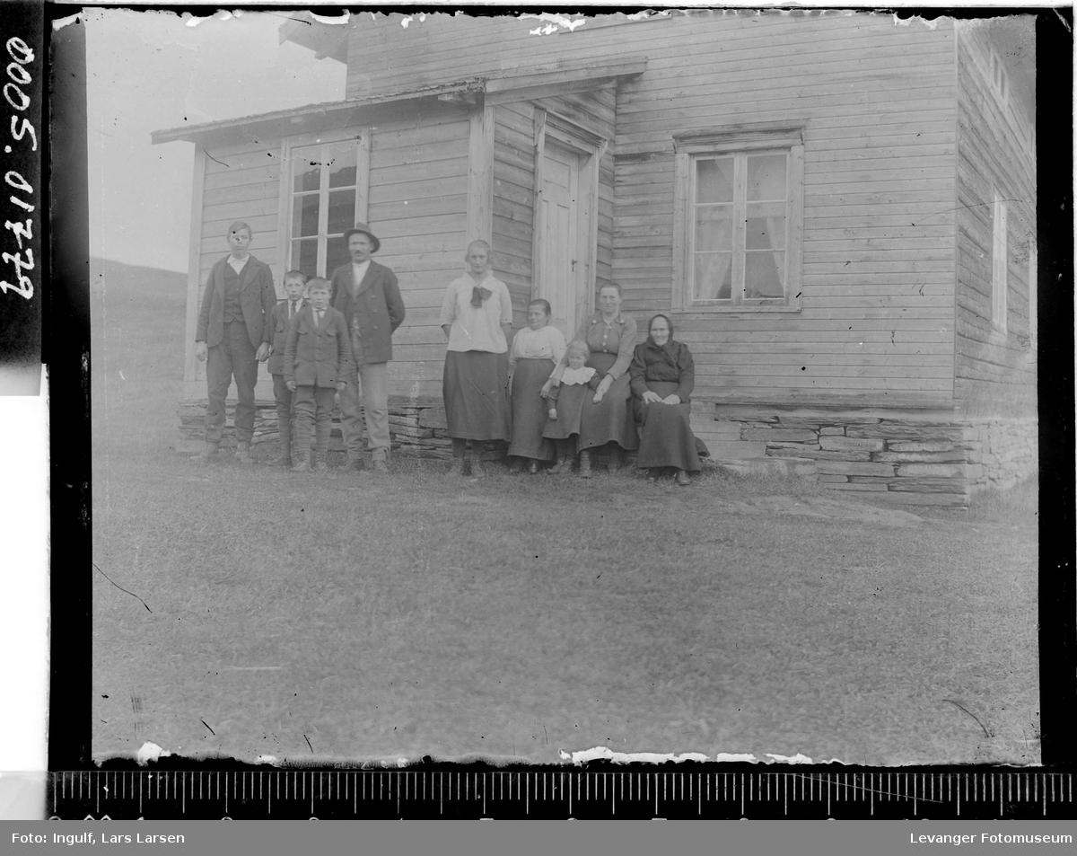 Gruppebilde av to menn, fire kvinner og tre barn foran en bygning.