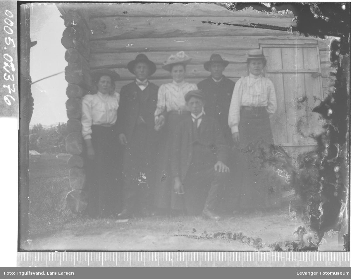 Gruppebilde av tre kvinner og tre menn i helfigur foran en bygning.