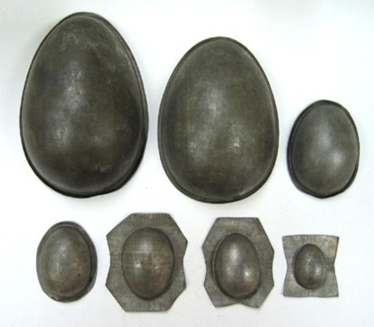 7 enkla formar i äggform. Måtten som är angivna gäller höjden på äggformen.  Formar för tillverkning av chokladägg (halvor).  Rörelsen lades ned 1982.