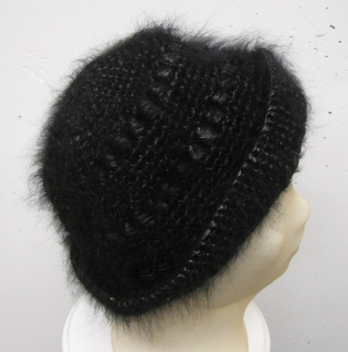 Svart hatt i angora och bast med ett 4 cm, brett brätte vilket är uppvikt runt om.    Hatten är mycket mjuk och ''oformlig'' varför diameter måttet  är mycket ungefärligt.    Givaren var bosatt i Skara åren 1938-1958.