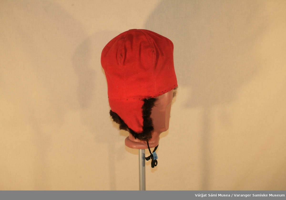 Damelue i rødt klede med skinnbesetning. Inni er den foret med sort boblestoff. På toppen en knapp som er trukket med rødt klede. Skinnkanten som er sydd rundt lua er av mørkebrunt skinn, kanskje av mår.