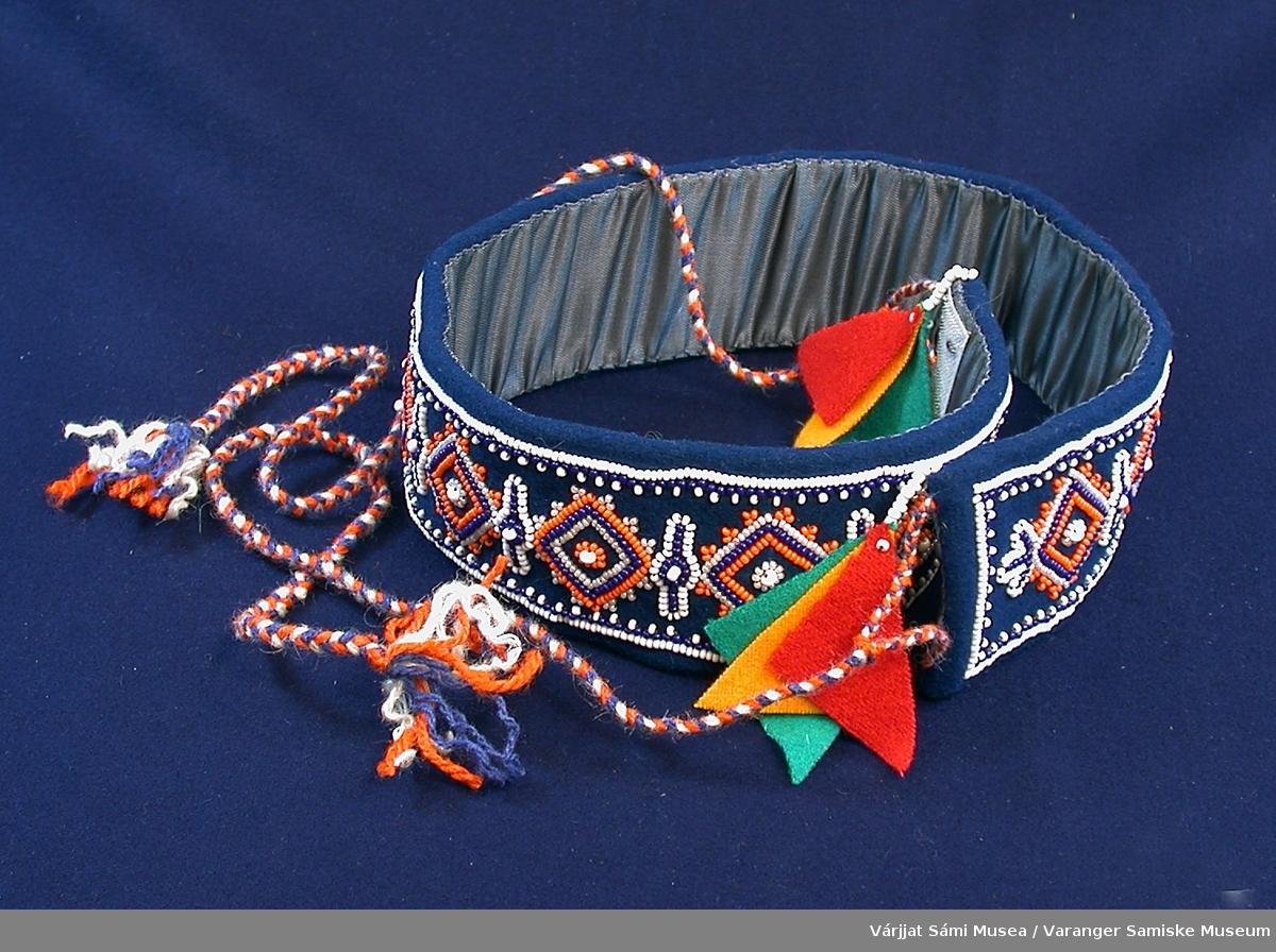 Belte av blått klede med perlebroderi. Beltet er fôret med et silkeblankt stoff i samme blåfarge som kledet. Perlene er små glassperler i hvitt, blått, oransje og svakrosa (skyrosa). Mønsteret er rombeformet. I endene av beltet er det to snorer av tvunnet ullgarn i oransje, hvitt og blått. I endene av snorene henger det en dusk av klede som består av tre trekanter i rødt, gult og grønt, tilsammen 2 dusker.