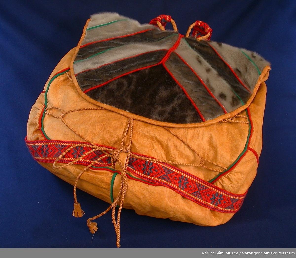 Ryggsekk av glatt reinskinn, selskinn m/hår, klede og ullbånd. Hovedrommet er sydd av reinskinn, alle sømmer er kantet med kelde i rødt og/eller grønt. Lokker er sydd av selskinnsstykker der sømmene er kantet med rød og grønn klede. Sekken har hemper og snorer av tvunnet reinskinn med dusk i hver ende. Sekken skal bæres ved hjelp av et vevd ullbelte i rødt, grønt og gult, vevd av Katrine T. Nilsen.