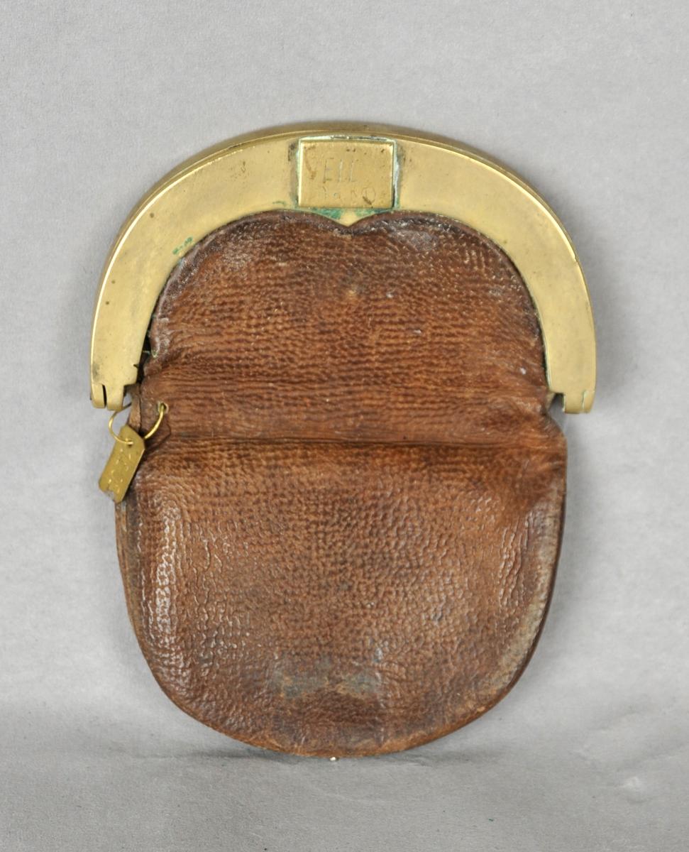 Pengepung av garva lær med lås av messing. Låsen er støypt, glatt. Låsen er ei firkanta  messingplate som er festa i ein fjør.