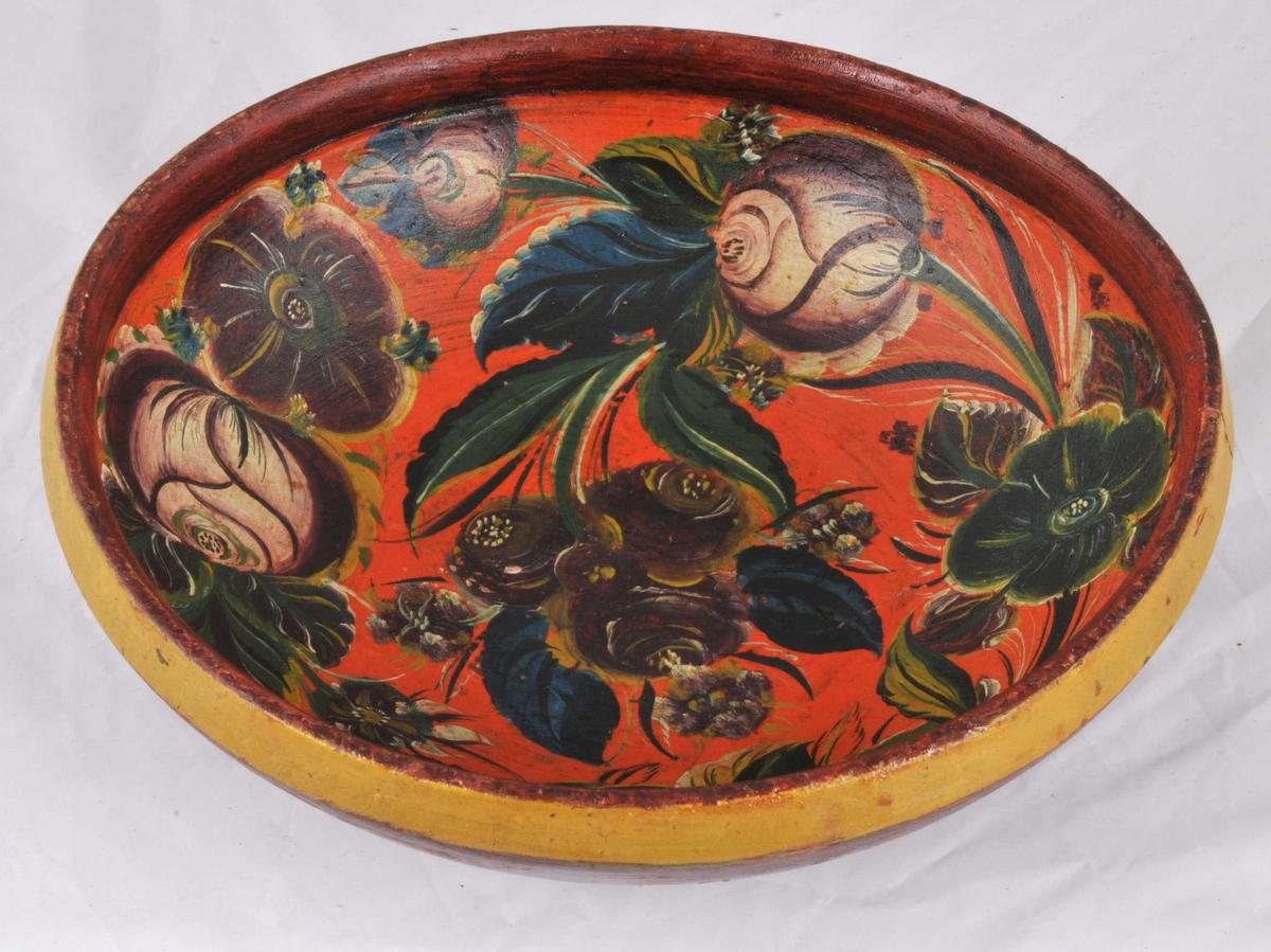 Bollen er mørk raud utvendig med gul kant, innvendig er botn i orange med lauklinknande blomar og naturalistiske blad. Raud kant.