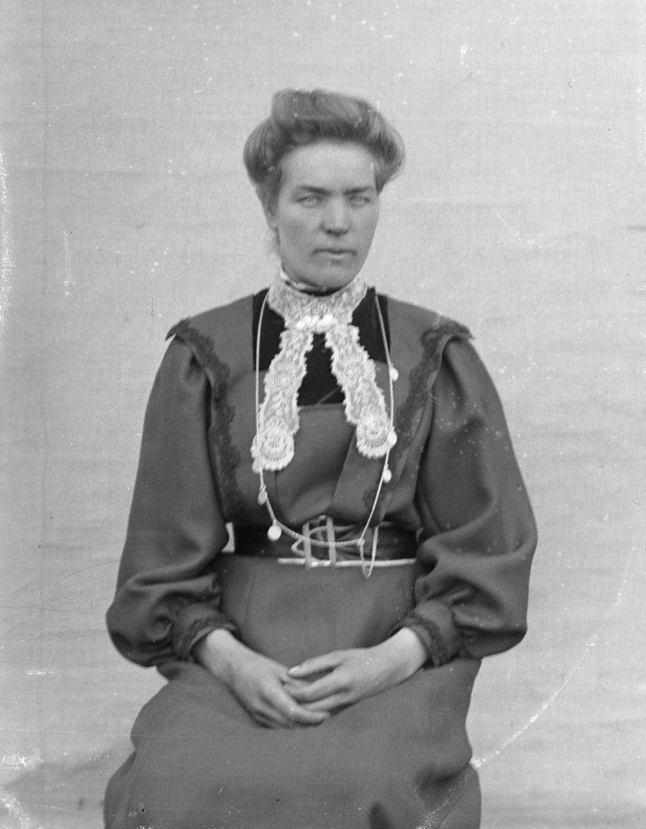 Kvinne kledd i mørk kjole, med kalvekryss, sittende foran lerret