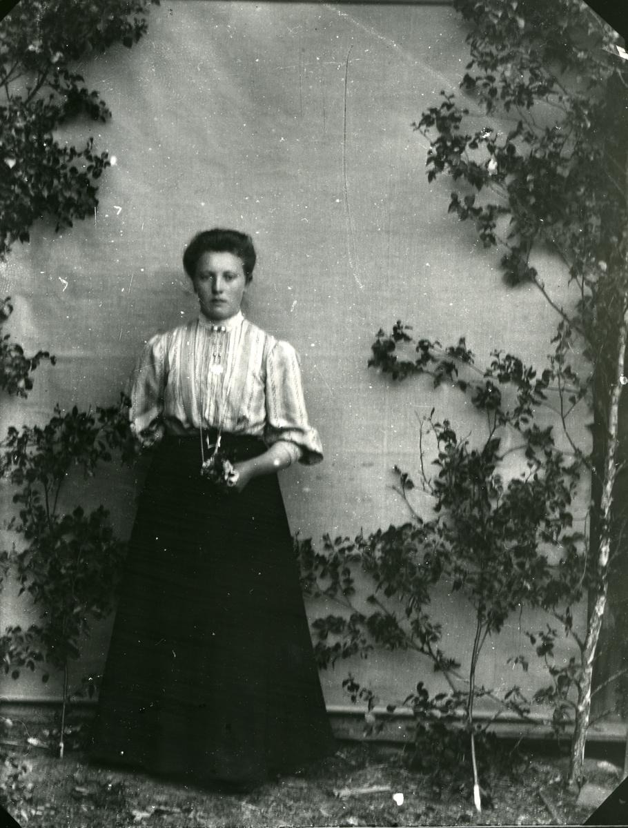 Kvinne i helfigur, fotografert stående med bjørkekvister og lerretbakgrunn