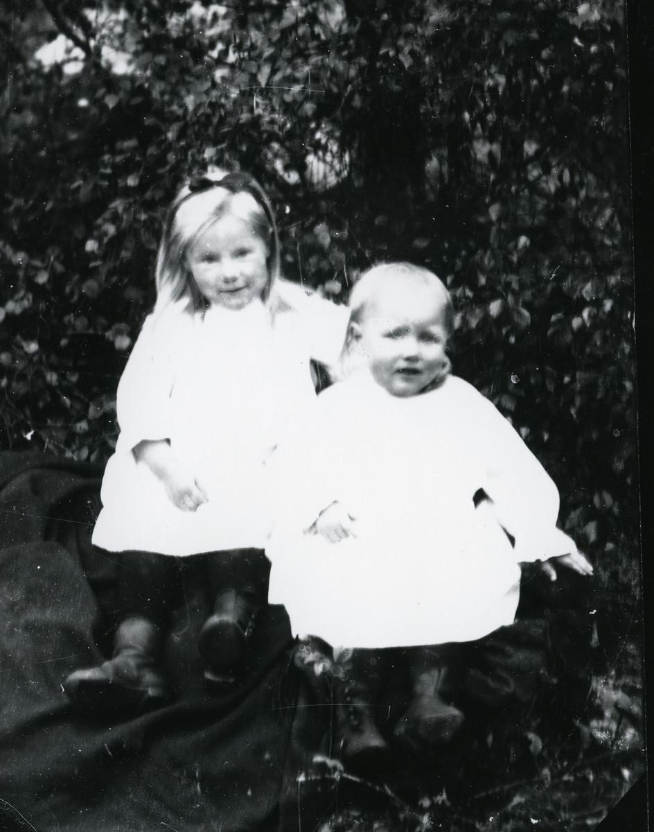 To barn kledd i lyse kjoler, trær i bakgrunnen