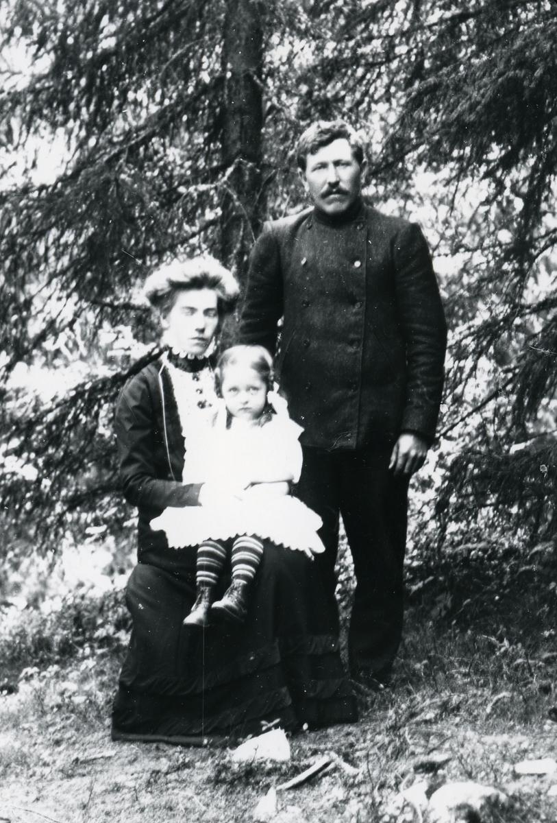 Kvinne på stol, med liten jente på fanget, og mann stående ved siden av. Skog i bakgrunnen