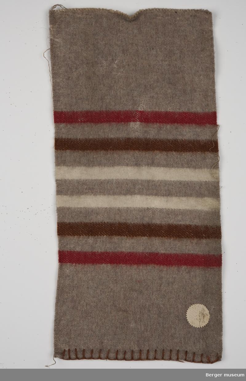 En prøve. Ensfarget brunmelert med striper i rødt, brun og hvit offwhite. Stripene er like brede.