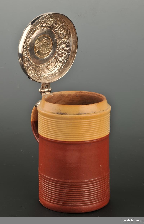 Drevne rokokkoornamenter rundt en sølvmynt, på mynten Christian V's profil med innskrift. Lokkåpneren som en havhest