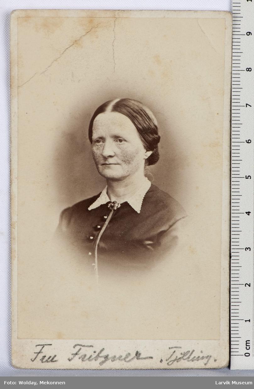 kvinne, halvprofil, mørk drakt m/hvit krave knapper og brosje