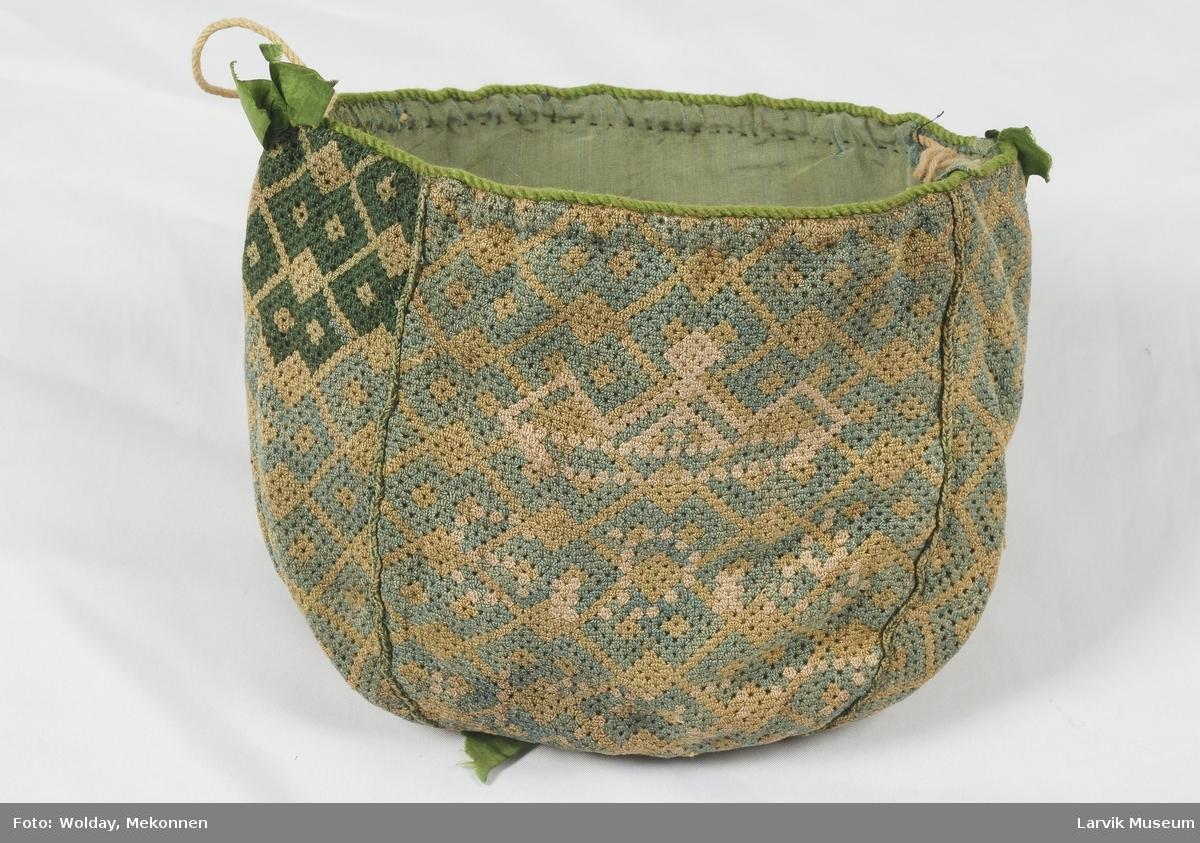 Form: Satt sammen av 4 kileformede stykker, kantet med grønn snor, foret med grønn silke, løpegang og sammentrekksnor øverst.sløyfer i silke.