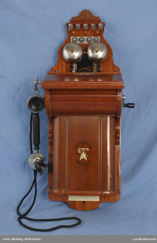 Form: Telefon kasse med lokk til å åpne. Telefon røret henger ved siden av. sveiv på andre siden.
