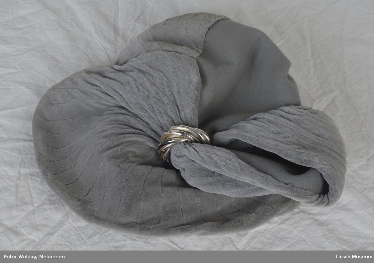 Form: Alpeluetype, På sydd fløyel som er snurpet sammen på midten med en plastring- Det hele skråner oppover, bakover.