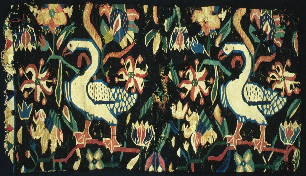 """Åkdyna vävd i flamsk. Huvudmotiv är två stora ljusa gäss med blå konturer och röd näbb, båda vända åt vänster. Fåglarna omges av strödda blommor bl.a. tulpaner. Bård i kortsidorna av triangelformer. Brunsvart botten, blommor i två gröna och två blå nyanser, samt gult, beige och rött. Varp i 2-trådigt s-tvinnat lingarn, 6 trådar/cm. Inslag i 1-trådigt, s-spunnet ullgarn, enkelt eller två trådar tillsammans samt i 2-trådigt z-tvinnat ullgarn. Inslagstäthet: 12-18 inslag/cm, beroende på grovlek. Baksida vävd i tunn rips med bomullsvarp och ullinslag. Smala dukagångsränder. Halva tyget är mycket blekt. Dynan är öppen i ena kortsidan. Eventuellt är den nedminskad i storlek/avklippt? Plomberad efter malbehandling. Lapp medföljer vävnaden: """"Skänkt till Malmöhus Läns Hemslöjdsförening, Helsingborg, Hermine Andersson."""