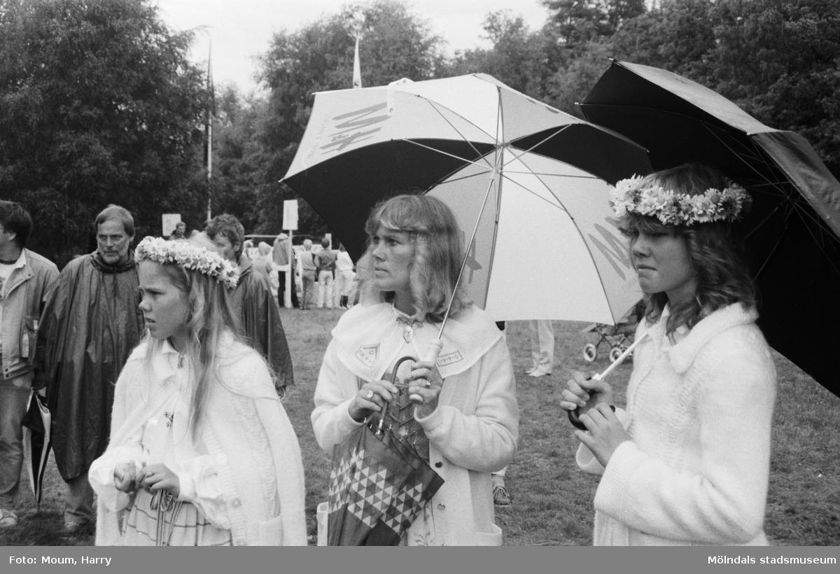 """Midsommarfirande på Ekensås i Kållered, år 1984. """"Ingela, Viktoria och Johanna Grimmefält firade midsommar i strilregnet på Ekansås.""""  För mer information om bilden se under tilläggsinformation."""