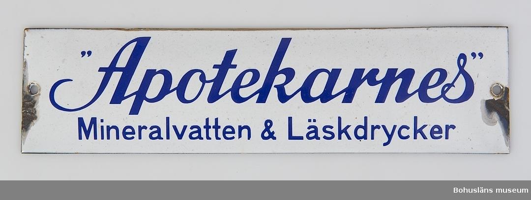 """Emaljskylt. Blå text på vit botten: """"Apotekarnes""""  Mineralvatten & Läskedrycker."""" Skador på sidorna. Okänd proveniens.  Inköpt hos F. Nordbergs antikaffär, St. Hellevigsgatan, Uddevalla."""
