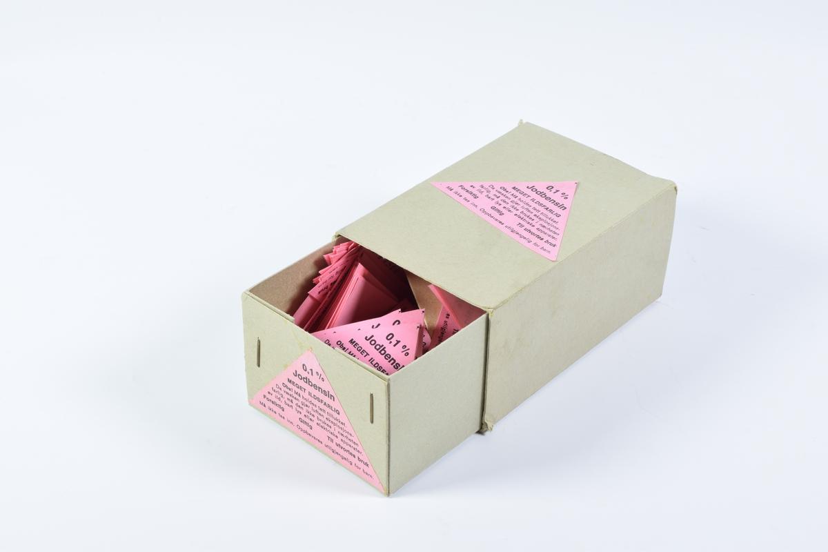 """Fire esker og en rull med etiketter. Eskene består av to separate deler, hvor den ene ligger inne i den andre og kan skyves ut. De innerste eskene er stiftet sammen i hjørnene. Etikettene er trekantet og rosa med sort skrift. Et eksemplar av hver etikett er limt på en av kortsidene og en eller to av de andre sidene på hver eske.  Eske a er i grå papp og inneholder etiketter for """"Jodbensin 0,1%"""".  Eskene b og c er i hvit papp og inneholder etiketter for """"Bensin"""" Etikettene har en enkel bord.  Eske d er i hvit papp og inneholder etiketter for """"Aceton"""". Etikettene har en enkel bord.  Rull e har rektangulære etiketter for """"Borvann"""". Etikettene er røde og hvite med sort skrift. Øverst i det venstre hjørnet er et Hygiea-beger omkranset av en slange. Etikettene er klistremerker."""