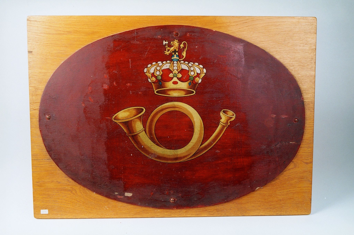 Postmuseet, gjenstander, skilt, ovalt postskilt, posthorn og krone med riksløve (postlogo) malt på en plate, kronen har svensk flaggfarge under løven.